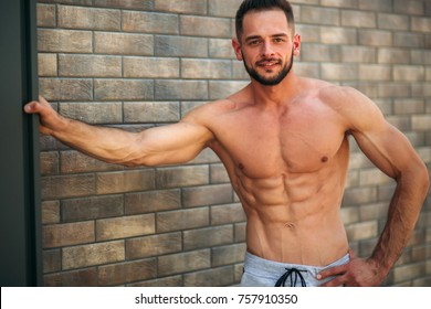 Young athlete posing with a torso for photography on a brick wall background. Bodybuilder, athlete with pumped muscles, breast and arm rescue