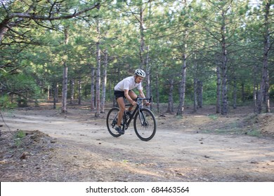 Young athlete riding on his professional mountain or cyclocross bike in the forest