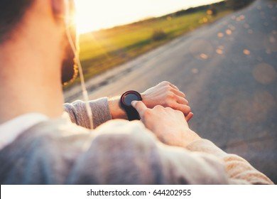 Young athlete runner in headphones looks at a modern smart clock and counts up spent calories after training outdoors at sunset
