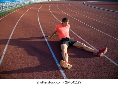 young athlete sits on the track stadium after jogging