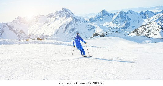 Young athlete skiing in Deux Alps french mountains on sunny day - Skier riding down for winter snow sport competition - Training and vacation concept - Focus on him - Warm filter