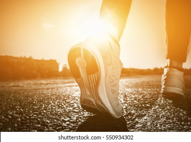 Young athlete in sneakers makes summer morning workout and exercises. Running on the move close-up on a background of the rising sun. Sports and healthy lifestyle.