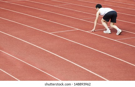 young athlete is at the start of the line at the stadium
