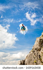 Young athlete walking on a slackline - tight rope betweend two rocks. Beautiful highline scene in mountain area on a sunny day with fluffy clouds