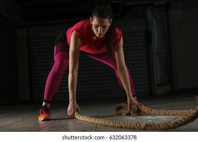 Young athlete woman is training with rope in garage.
