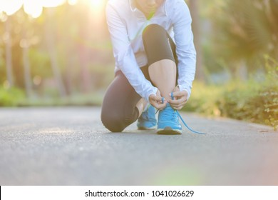 Young athlete woman tying running shoes in the park outdoor, female runner ready for jogging on the road outside, asian Fitness walking and exercise on footpath in morning. wellness and sport concepts