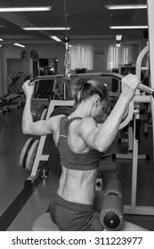 Young athlete working on your back muscles. Bench scales neck. Work on tell muscles. Beautiful blonde in the gym. Weight training.