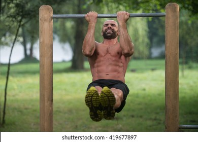 Young Athlete Working Out Biceps In An Outdoor Gym - Doing Street Workout Exercises