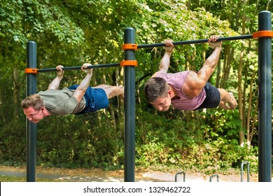 Young athletes hanging belly-down parallel to the ground, back lever workout on horizontal bar for body mastery on sunny day in summer.