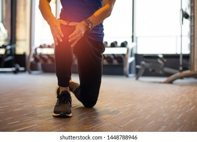 Young athletes have a right knee injury during exercise at fitness room.