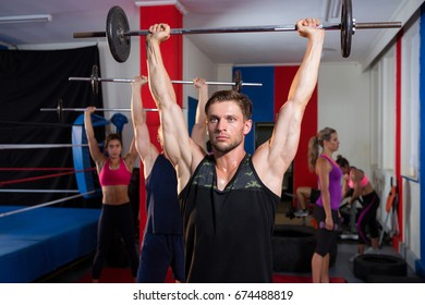 Young athletes lifting barbells with arms raised at fitness studio