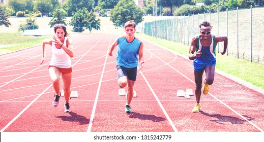 Young athletes on running track - Active woman challenging men friends in sport race - Concept of gender equality - Focus on black man - Vintage filter look image