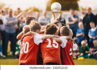 Young Athletes from School Sports Team Holding Winning Trophy. Kids Champion Sport Team. Boys Holding Prize Cup. Children Rising Winner Golden Cup. Boys Celebrating Sports Championship