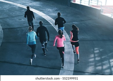 Young athletes in sportswear training in gym and running on race track.