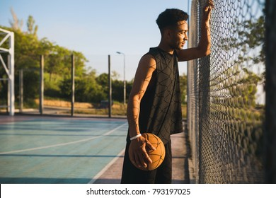 young athletic black man standing on court on sunrise with ball, basketball game player, morning exercises,  active healthy lifestyle, hot summer day, resting