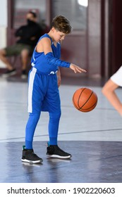 Young athletic boy playing in a game of basketball