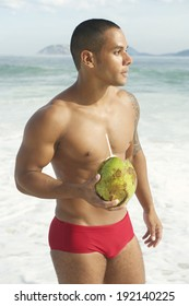 Young athletic Brazilian carioca man holding green drinking coconut on the beach in red sunga bathing suit Rio de Janeiro Brazil