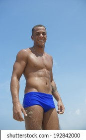 Young athletic Brazilian carioca man standing smiling looking at the camera on the beach in blue sunga bathing suit Rio de Janeiro Brazil