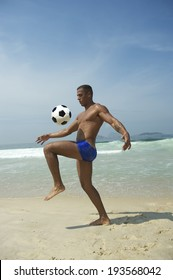 Young athletic Brazilian carioca man kicking football soccer ball on the beach in blue sunga bathing suit Rio de Janeiro Brazil