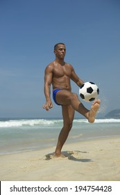 Young athletic Brazilian carioca man juggling football soccer ball on the beach in blue sunga bathing suit Rio de Janeiro Brazil