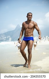 Young athletic Brazilian carioca man standing on Ipanema Beach in blue sunga bathing suit in front of Two Brothers Mountain Rio de Janeiro Brazil
