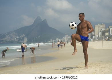 Young athletic carioca man Brazilian altinho player juggling football soccer ball on the beach in blue sunga bathing suit Rio de Janeiro Brazil