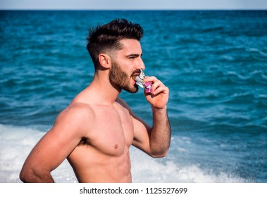 Young athletic confident man biting chocolate or protein bar on background of sea or ocean in summer