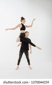 Young Athletic Couple Performing Art Dance Element. Man Stand Straight, Woman Dancer Sit on Partner Shoulder. Perfomer in Black Denim Looking at Side Isolated on White Background