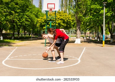 Young Athletic Couple Playing Basketball Together on Outdoor Court in Lush Green Park