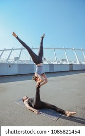 Young athletic couple practicing acroyoga at stadium urban style.Balancing in pair. Fit active pair yoga time.Sporty handsome man supporting slim beautiful brunette woman.Training time.Asana