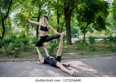Young athletic couple practicing acroyoga in park urban style.Balancing in pair. Fit active pair yoga time.Sporty handsome man supporting slim beautiful brunette woman.Training time.Asana