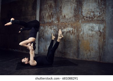 Young athletic couple practicing acroyoga. Balancing in pair. Fit active pair yoga time. Sporty handsome man supporting and holding slim beautiful brunette woman. Training time. Asana