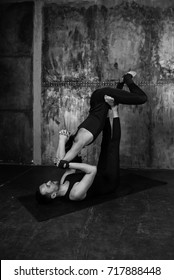 Young athletic couple practicing acroyoga. Balancing in pair. Fit active pair yoga time. Sporty handsome man supporting and holding slim beautiful brunette woman. Training time.Asana.Black and white
