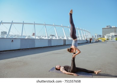 Young athletic couple practicing acroyoga at stadium urban style.Balancing in pair. Fit active pair yoga time.Sporty handsome man supporting slim beautiful brunette woman.Training time. Asana