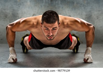 Young athletic fighter doing push ups in grunge environment./Push-up