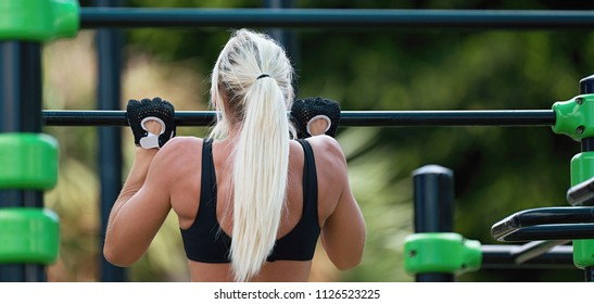 Young athletic fitness woman working out at outdoor gym,fit woman doing pull-ups