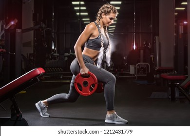 A young athletic girl does exercises using sports equipment.