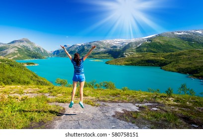 Young athletic girl, enjoying beautiful views of the mountains, snow-capped peaks on a journey to fjords Norway.