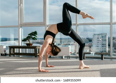 Young athletic girl makes chakrasana pose in the white yoga studio with panoramic windows overlooking the city.Concept of healthy lifestyle.