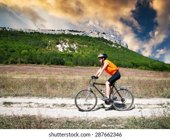 young athletic girl rides a bicycle on a mountain road at sunset