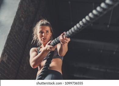 Young athletic girl with a rope in cross-training