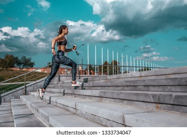 Young athletic girl running morning for jog fitness training, sportswear, leggings and top. Phone listens music headphones. Summer city workout, online playlist application to Internet. Free space.