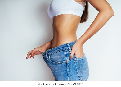 a young athletic girl shows her flat stomach, quickly lost weight and jeans became her big