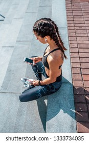 Young athletic girl sitting, sportswear, leggings top. In hand, phone listens music headphones. In summer city rest after training, fitness workout online application social networks chat Internet.