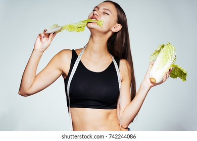 a young athletic girl watches her figure, eats a healthy low-calorie Peking cabbage