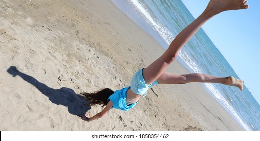 young athletic girls while doing exercises and pirouettes on the seashore in summer