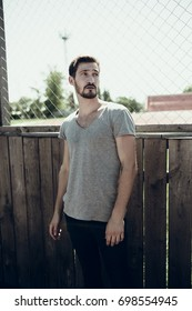 young athletic guy with a beard posing in the autumn Park and the stadium. slim figure and flat torso. Wallpapers for your desktop. street style: skinny jeans and t-shirt. emotional portraits