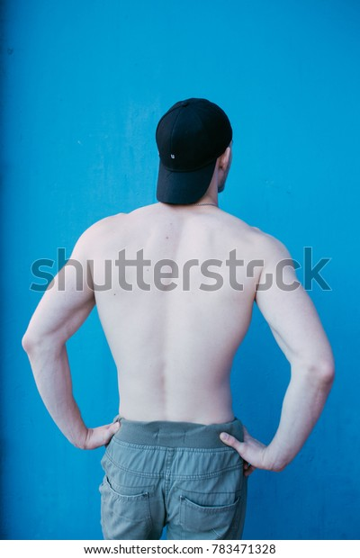 young athletic guy with an athletic body and bald head. sweat pants and naked torso. posing around a house. emotional portrait. broad back and a man's ass
