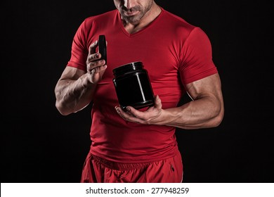 a young athletic guy holding an open jar of sports nutrition