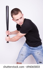 young athletic guy in jeans holding in his hand a baseball bat. the brutal image. clear skin and short hair. Wallpaper for desktop.male ass